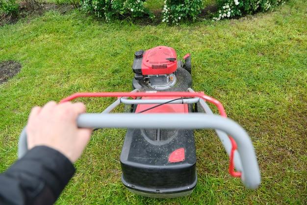 Tondeuse à gazon de travail sur la pelouse verte avec de l'herbe coupée.