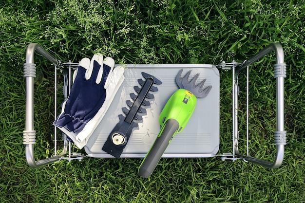 Tondeuse de jardin électrique avec accessoire et gants sur la chaise haute