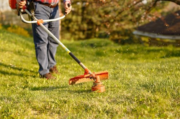 Tondeuse tondeuse - travailleur coupe l'herbe dans une cour verte au coucher du soleil.