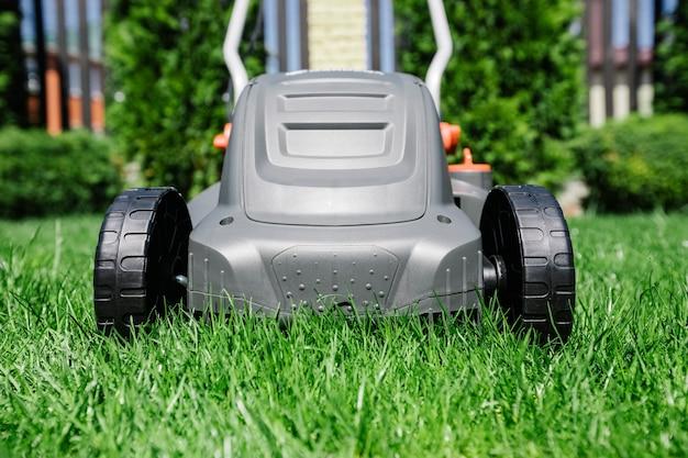 Tondre la pelouse d'été dans le jardin avec une tondeuse à gazon