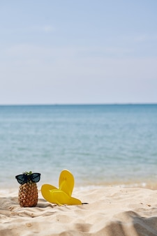 Tongs et ananas sur la plage