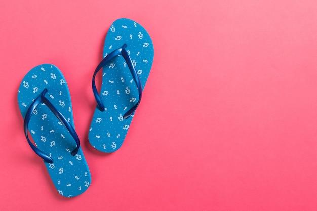 Tongs bleues sur fond rose. vue de dessus avec espace copie