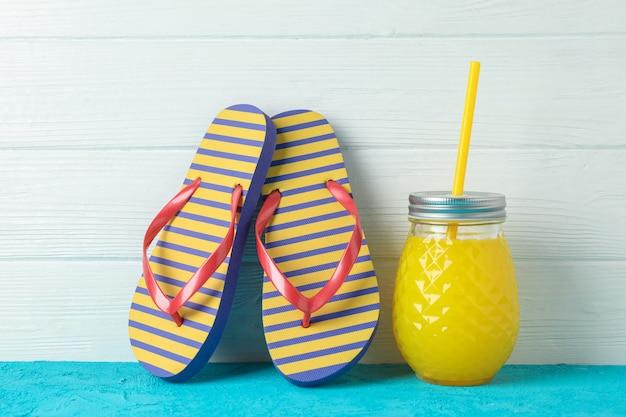 Tongs et bocal en verre avec du jus de fruits frais sur une table de couleur contre un mur en bois blanc, espace pour le texte. concept de vacances d'été