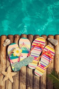 Tongs sur bois contre l'eau bleue concept de vacances d'été