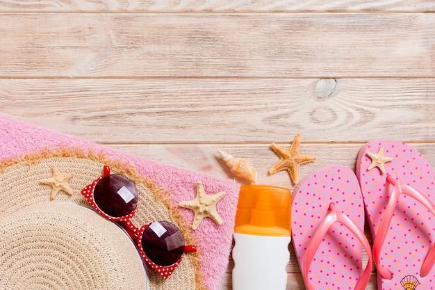 Tongs, chapeau de paille, étoile de mer, bouteille de crème solaire, spray de lotion pour le corps sur bois