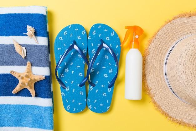 Tongs, chapeau de paille, étoile de mer, bouteille de crème solaire, spray de lotion pour le corps sur fond jaune vue de dessus. fond plat d'accessoires de mer plage d'été, concept de voyage.