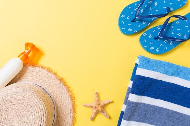 Tongs, chapeau de paille, étoile de mer, bouteille de crème solaire, spray de lotion pour le corps sur jaune