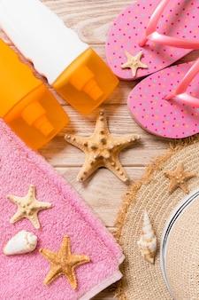 Tongs, chapeau de paille, étoile de mer, bouteille de crème solaire, spray de lotion pour le corps sur la vue de dessus de fond en bois. fond plat d'accessoires de mer plage d'été, concept de voyage.