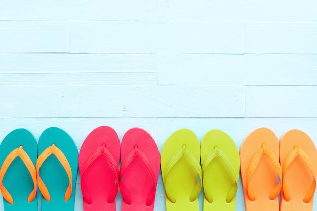 Tongs colorés sur fond de bois pastel bleu clair pour le concept de l'été.