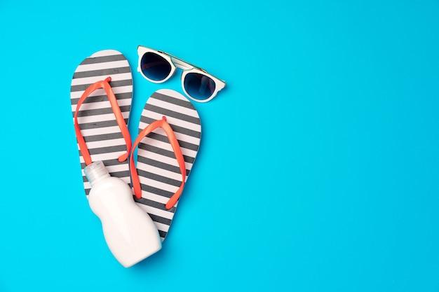 Tongs avec crème solaire et lunettes de soleil sur fond bleu, plat