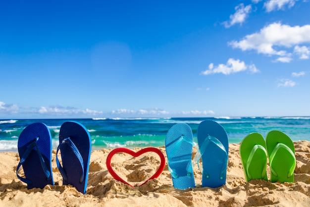 Tongs en forme de cœur sur la plage de sable