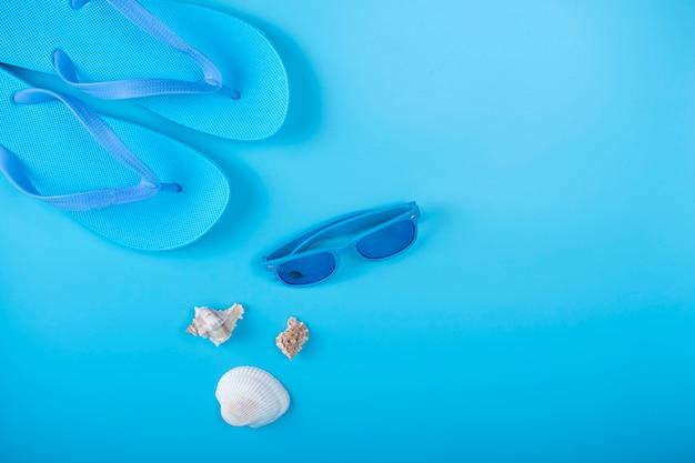 Tongs, lunettes de soleil et coquillage sur bleu
