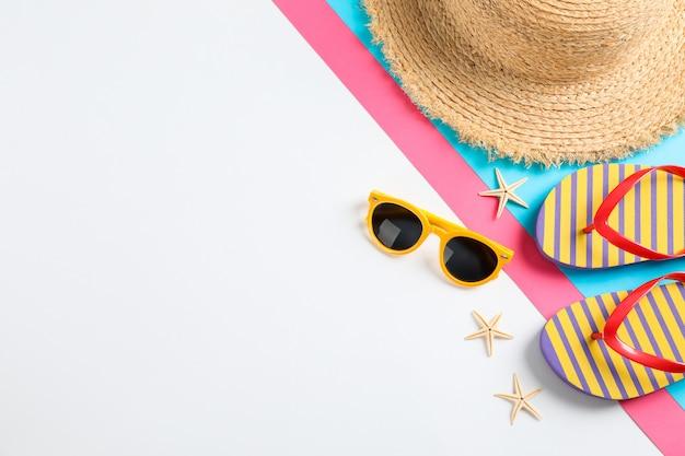 Tongs, lunettes de soleil, étoiles de mer et chapeau de paille sur la table des couleurs