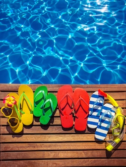 Tongs multicolores sur des planches de bois sur fond de l'eau bleue