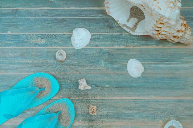 Tongs avec des objets marins sur bois.