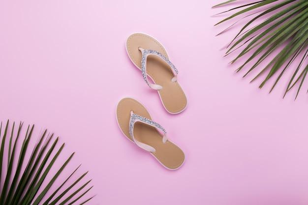 Tongs de plage de belle femme sur le fond rose pastel clair. concept d'été de plage et concept de vacances, vue de dessus