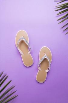 Tongs de plage de belle femme sur fond violet ou violet. concept d'été de plage et concept de vacances, vue de dessus