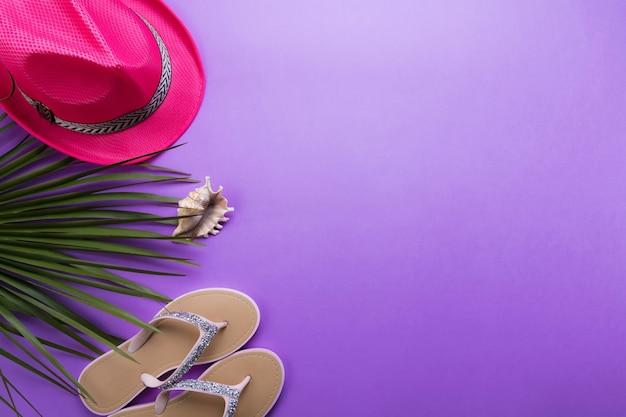 Tongs de plage de la femme sur le fond violet ou violet avec copie espace. concept d'été de plage et concept de vacances