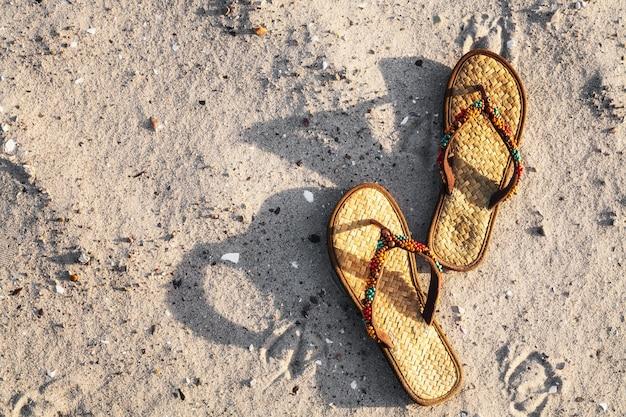 Tongs sur plage de sable, mer baltique, allemagne. concept de vacances d'été, vue de dessus, mise à plat