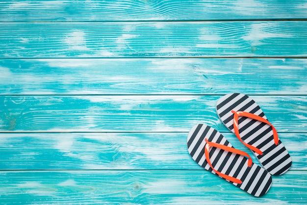 Tongs sur un plancher en bois bleu.