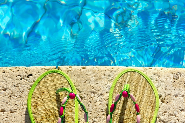 Tongs sur la plate-forme à côté de la piscine