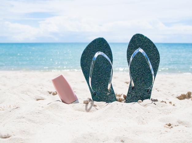 Tongs et protection solaire sur la plage de sable
