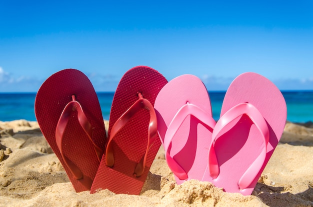 Tongs rouges et roses sur la plage de sable