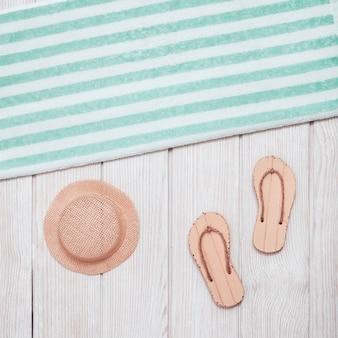 Tongs, serviette en coton à rayures bleues, chapeau du soleil sur bois blanc