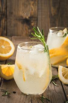 Tonique avec de la glace, du citron et du romarin sur une vieille table rustique en bois