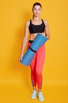Tonique jeune belle athlète femme aux cheveux noirs portant des vêtements de sport, debout et tenant un tapis de fitness bleu
