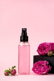 Tonique pour la peau rose dans une bouteille en plastique avec des fleurs de rose