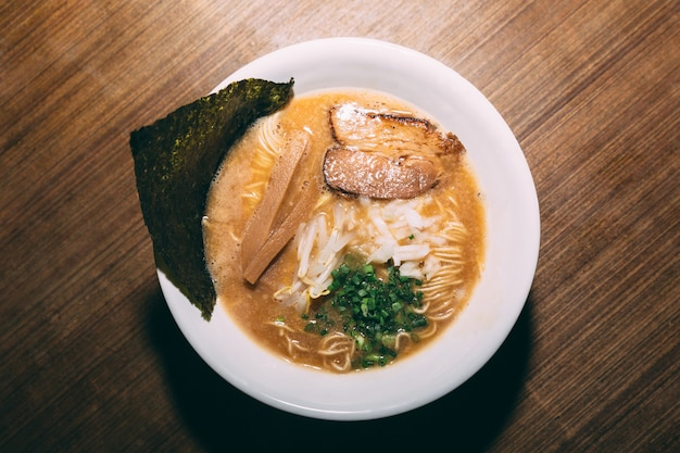 Tonkotsu ramen avec porc chashu, oignons verts, pousses, oignons, menma et algues séchées.