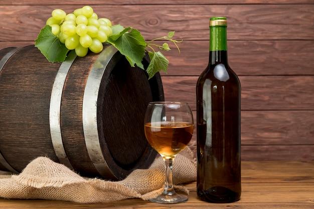 Tonneau en bois avec bouteille et verre de vin