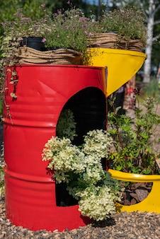 Tonneau en métal décoratif rouge et jaune avec des fleurs et de l'herbe utilisation décorative d'un vieux tonneau