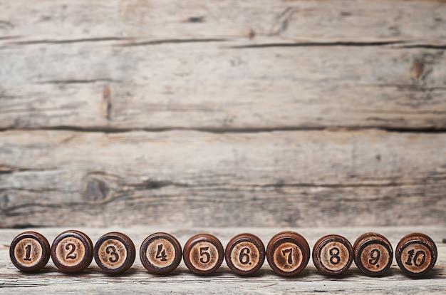 Des tonneaux en bois avec des nombres de un à dix sur un vieux fond en bois.