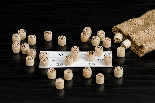 Tonneaux de loto en bois, carte de jeu et sac sur une table noire.
