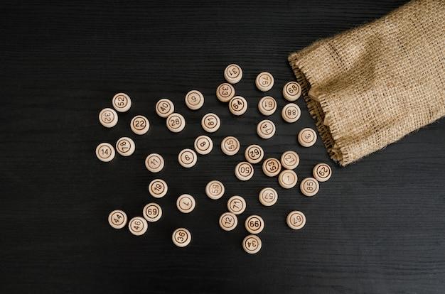 Tonneaux de loto en bois et sac sur une table en bois foncé