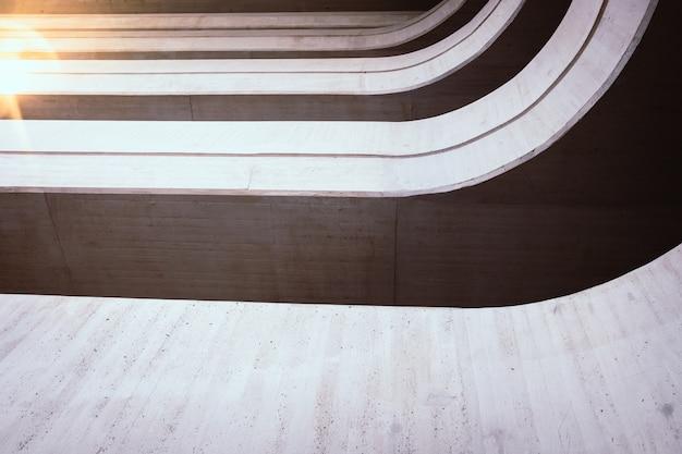 Des tons chauds à l'arrière-plan de l'intérieur d'une construction minimaliste de murs et de lignes à la texture rugueuse, illuminés par un rayon de soleil au coucher du soleil.