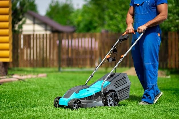 Tonte du gazon. travailleur coupant l'herbe dans une cour verte. un homme avec une tondeuse à gazon électrique tondant