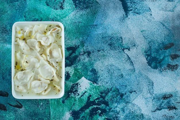 Toothsome dushbara dans une assiette sur bleu.