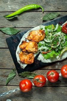 Top brochette de poulet servi avec oignons herbes fraîches tomates grillées et poivre sur tableau noir