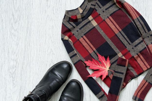 Top à carreaux avec manches et chaussures noires. feuille d'érable. concept à la mode.