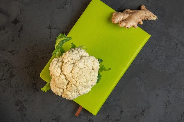 Top chou-fleur et gingembre sur une planche à découper verte sur dark