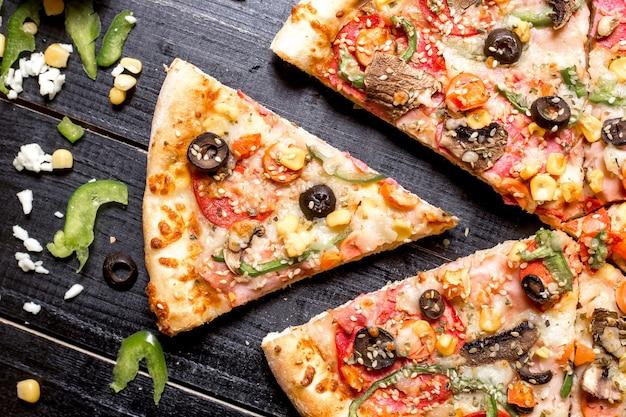 Top close up de tranche de pizza au pepperoni avec des pépites de sésame