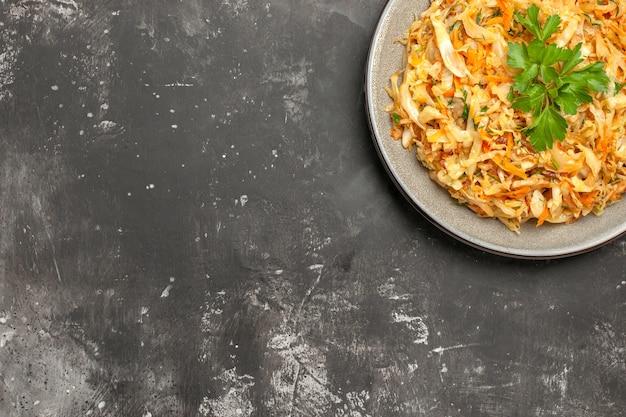Top close-up view chou assiette blanche d'herbes de chou sur la table