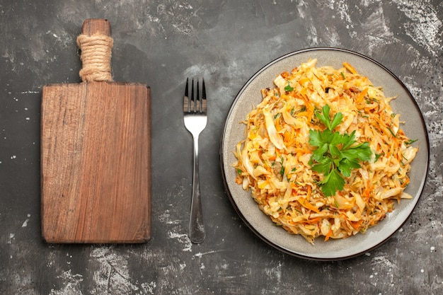 Top close-up view chou blanc assiette d'herbes carottes chou fourche la fourchette de coupe