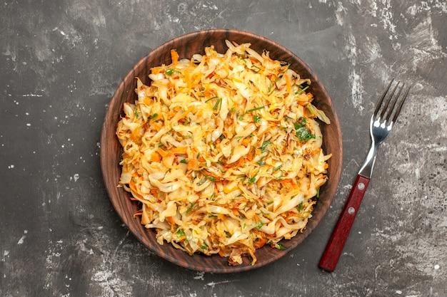 Top close-up view chou avec carottes l'assiette de la fourchette de carottes et chou appétissants