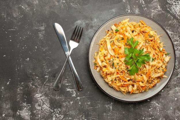 Top close-up view chou chou carottes herbes sur la plaque couteau et fourchette