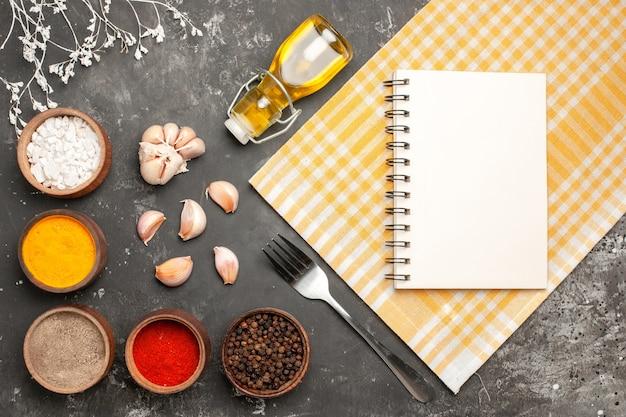 Top close-up view épices cahier sur la nappe à carreaux ail bouteille de fourchette à épices huile