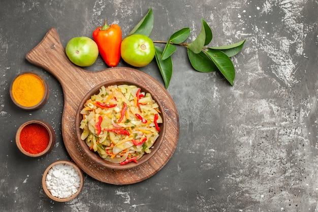 Top close-up view salade épices poivrons avec des feuilles à côté de la planche avec bol de salade